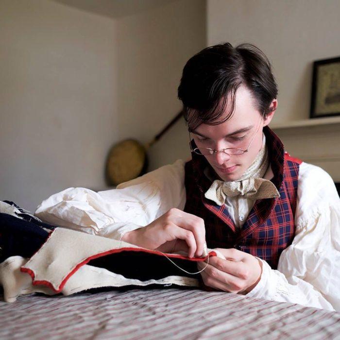 Zack Pinsent, chico que viste ropa vintage de 1820; hombre con lentes antiguos cosiendo ropa