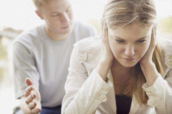 Hombre arrepentido con mujer tapándose los oídos porque no quiere escucharlo