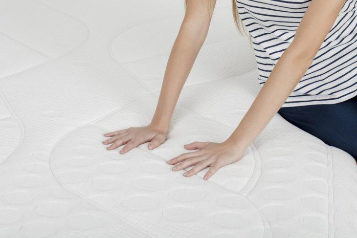 mujer tocando un colchón