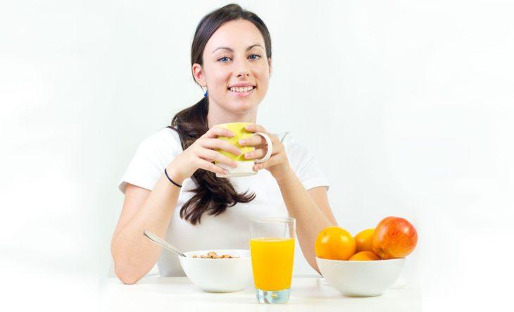 Mujer desayunando jugo, café, naranjas y cereal