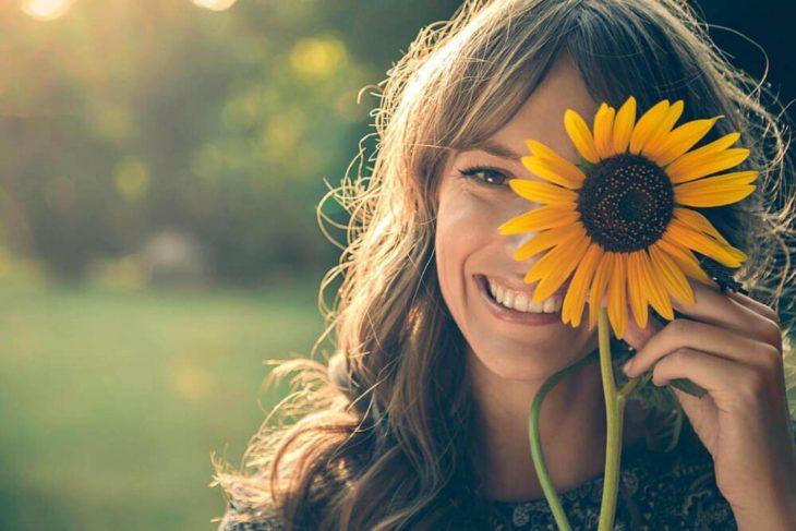 mujer rubia sonriendo con una flor de girasol en la mano