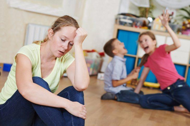 Mujer ama de casa con gesto agobiado cuidando dos niños