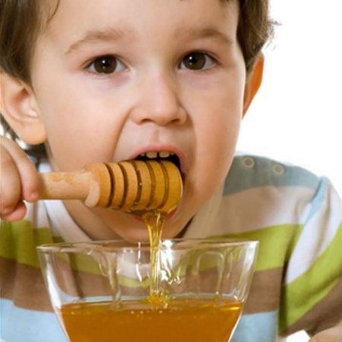 Niño de aproximadamente un año comiendo miel de abeja