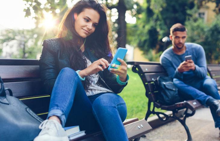 Mujer viendo el celular en un parque observada por hombre con celular