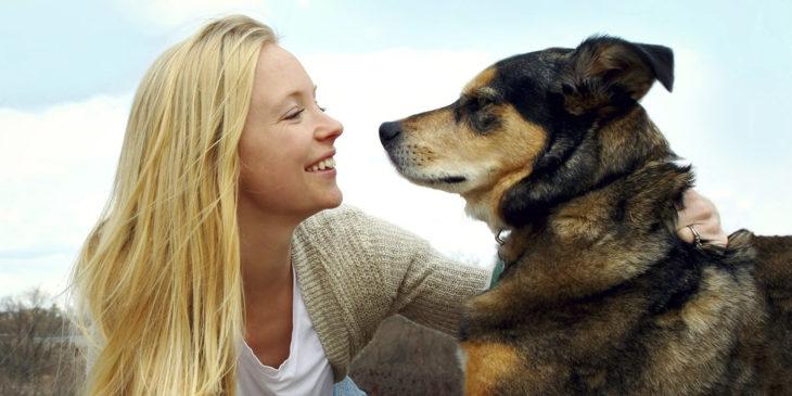 mujer sonriendo con un perro grande