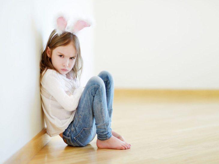 niña con diadema de orejas de conejo sentada de brazos cruzados con gesto de molestia