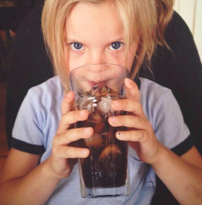 Niña bebiendo de un vaso de coca cola