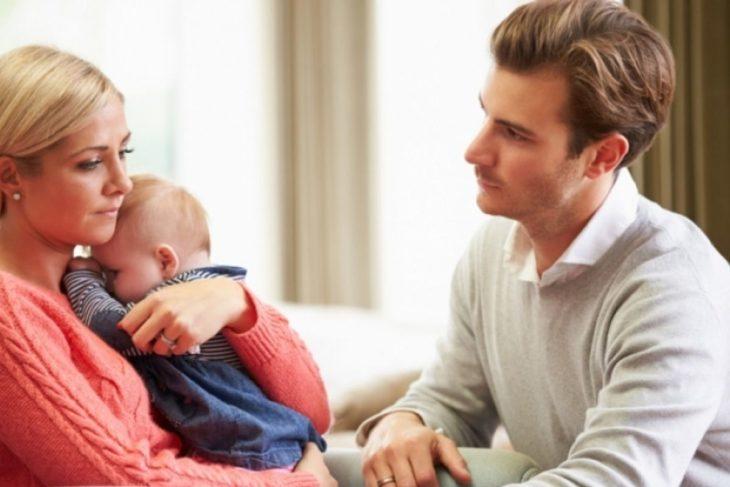 Mujer cargando a bebé y esposo viéndola, tienen rostros de infelicidad