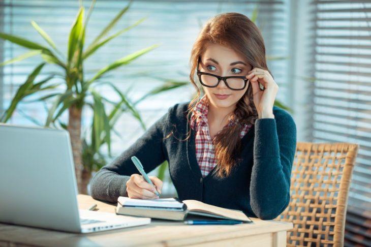 Mujer con lentes mirando la computadora