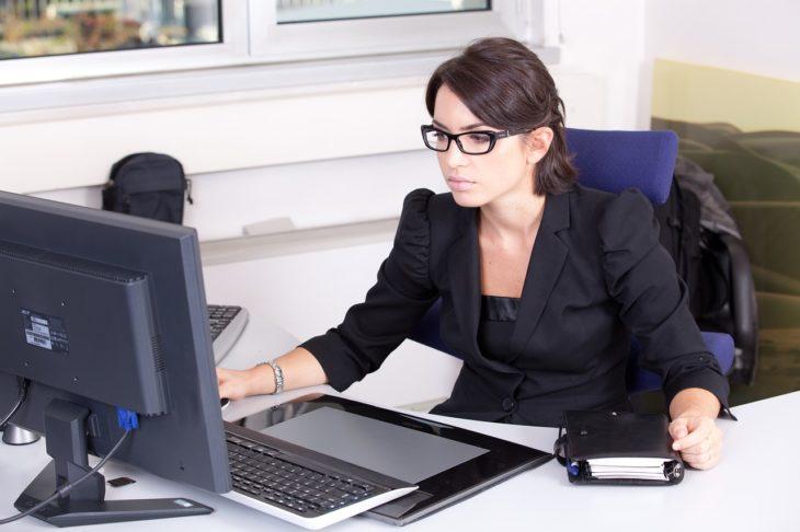 mujer de traje negro y lentes viendo su computadora de escritorio en una oficina