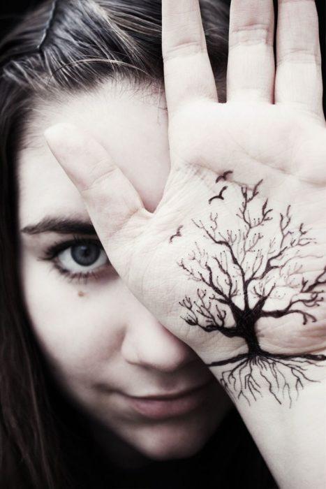 Chica con un tatuaje en las palmas de las manos en forma de un árbol sin hojas pero con pájaros