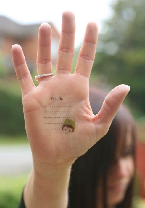 Chica con un tatuaje en las palmas de las manos en forma de lista para no olvidar los pendientes