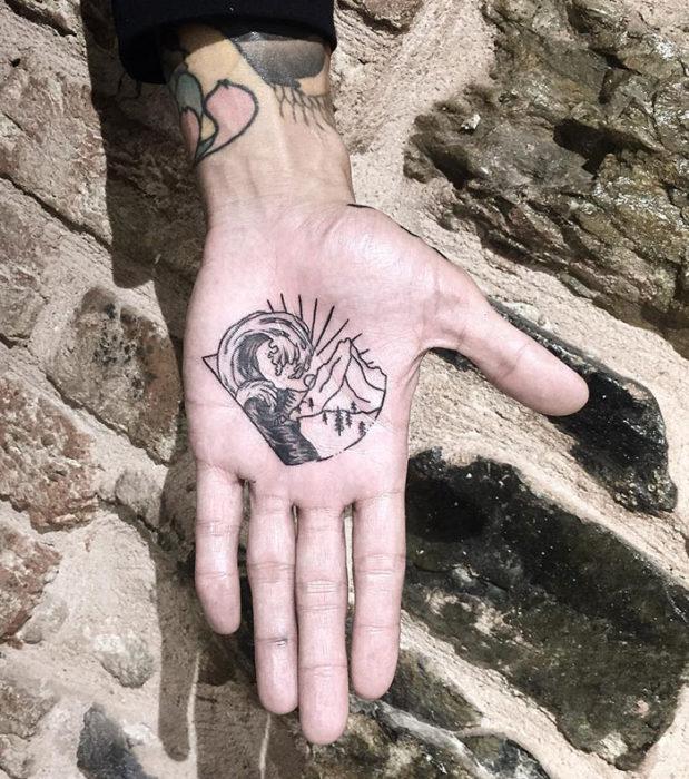 Chica con un tatuaje en las palmas de las manos en forma de unas olas del mar con los rayos del sol
