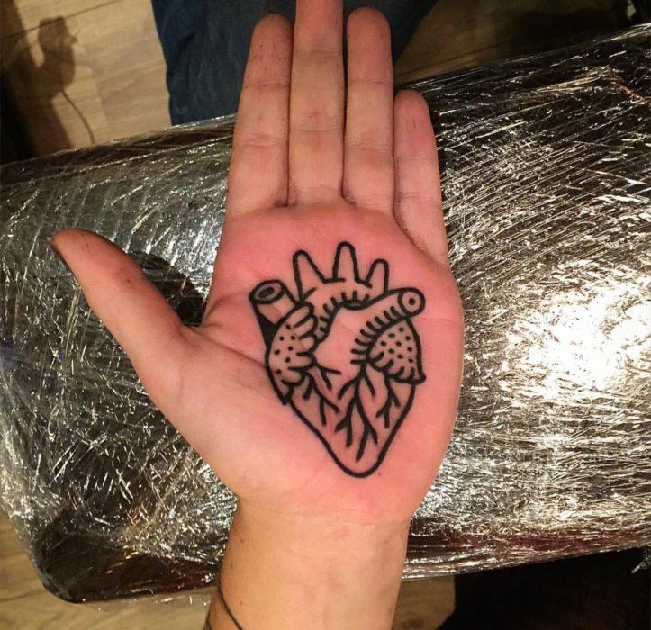 Chica con un tatuaje en las palmas de las manos en forma de un corazón