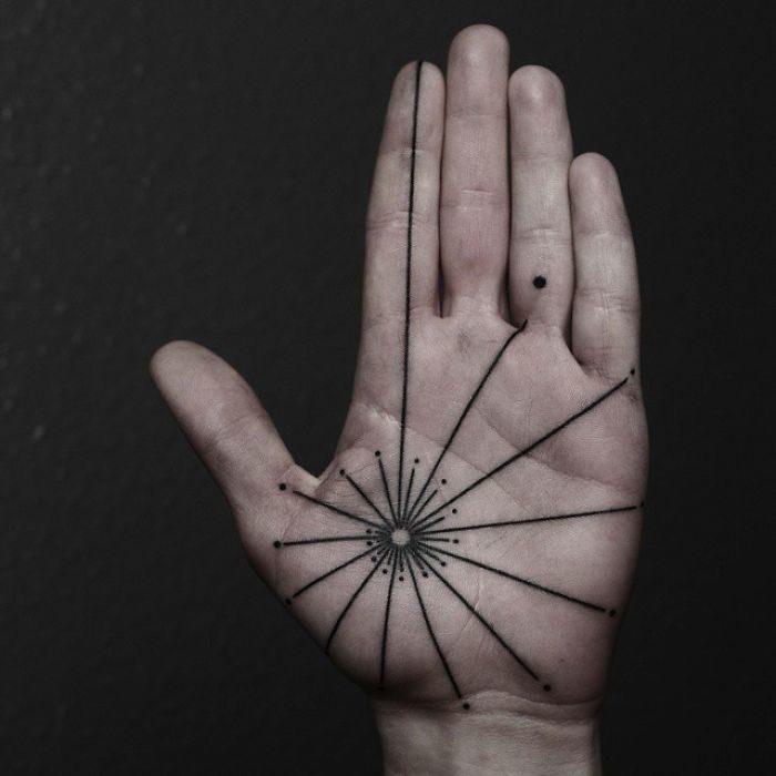 Chica con un tatuaje en las palmas de las manos en forma de puntos y líneas que van del centro a los dedos