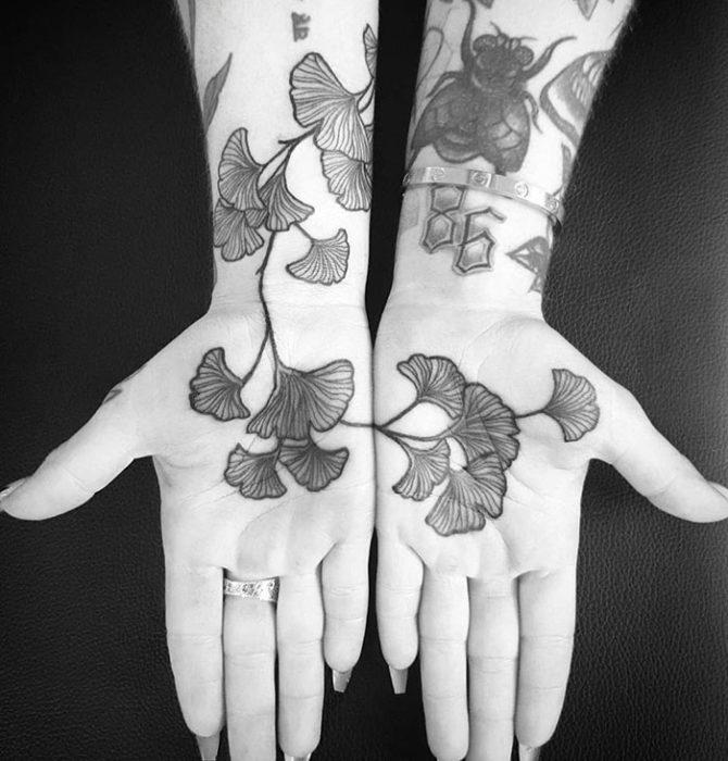 Chica con un tatuaje en las palmas de las manos en forma de flores