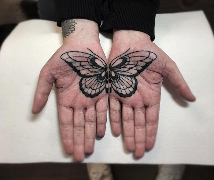 Chica con un tatuaje en las palmas de las manos en forma de una mariposa