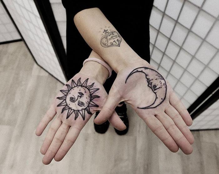 Chica con un tatuaje en las palmas de las manos en forma de sol y luna
