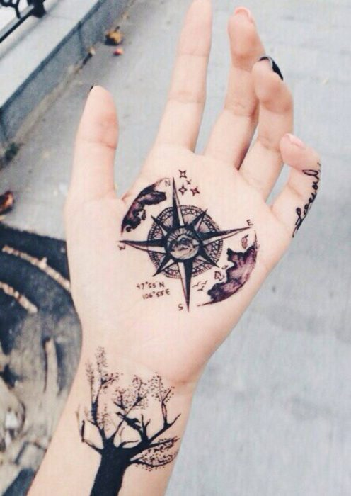 Chica con un tatuaje en las palmas de las manos en forma de rosa de los vientos con olas