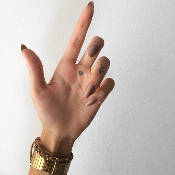 Chica con un tatuaje en las palmas de las manos en forma de un corazón cerca del dedo medio