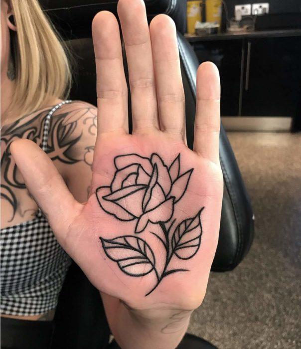 Chica con un tatuaje en las palmas de las manos en forma de una rosa