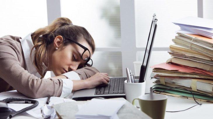Mujer dormida en oficina encima del escritorio