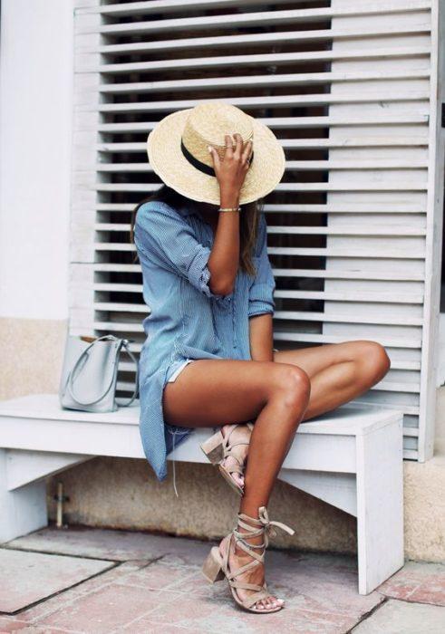 Chica sentada en una banqueta, cubriendo su rostro con un sombrero de paja