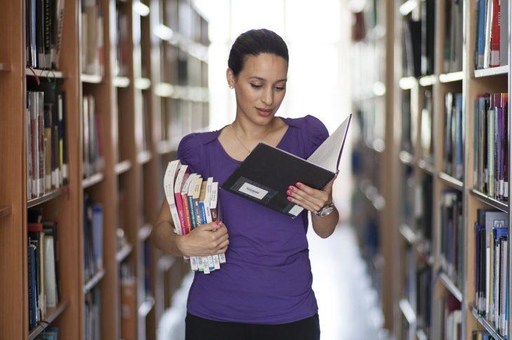 una joven en un pasillo de la biblioteca con varios libros en el brazo y uno que va leyendo