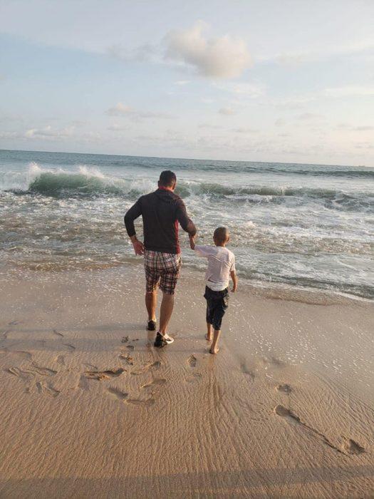Jonathan caminando por su padre a la orilla del mar