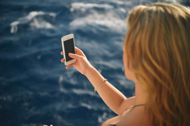 una toma desde atrás de una mujer que está frente al mar y tiene un teléfono celular en su mano