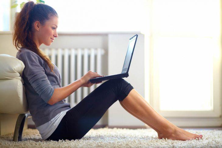 una mujer sentada en la alfombra con la computadora sobre las rodillas