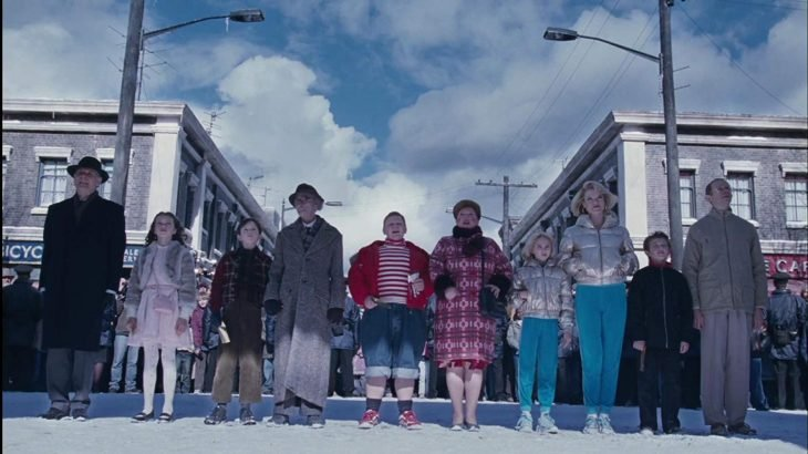 Niños junto a sus padres parados frente a la fábrica de Willy Wonka, escena de Charlie y la fábrica de chocolate