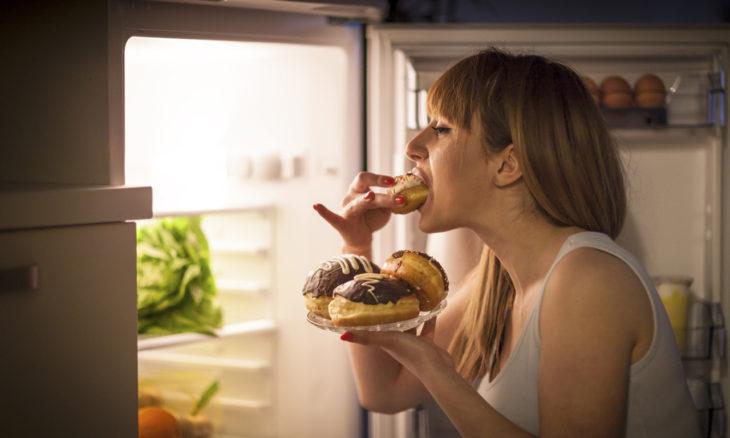 Mujer comiendo panes frente al refrigerador a altas horas de la noche