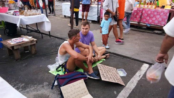 dos jóvenes occidentales sentados en medio de un mercado con carteles pidiendo dinero por que se quedaron sin recursos para viajar