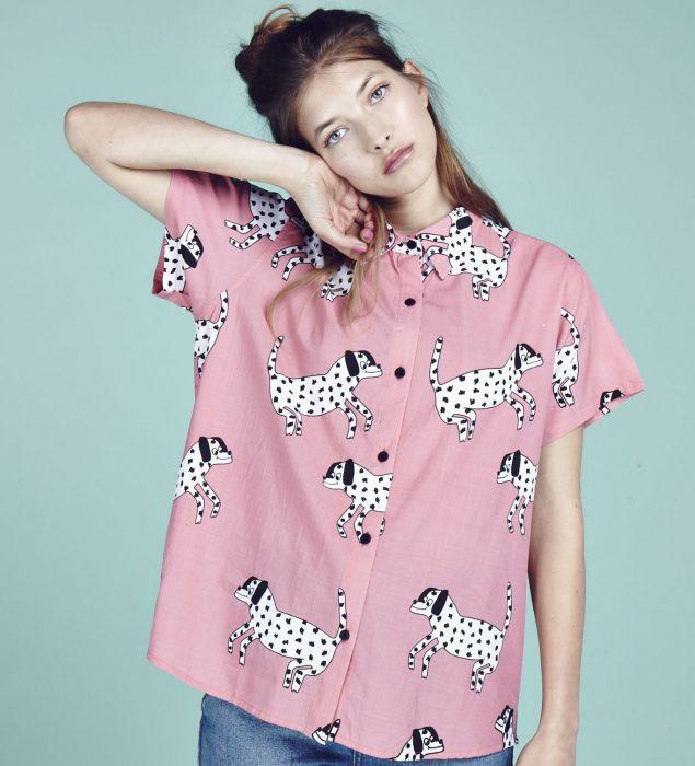 Blusas con estampados bonitos y kawaii; mujer de cabello castaño con camisa rosa con perros dálmata