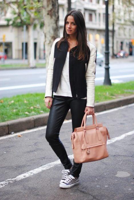 Chica parada en la calle durante una sesión de fotos y usando un outfit negro y bolsa de color rosa