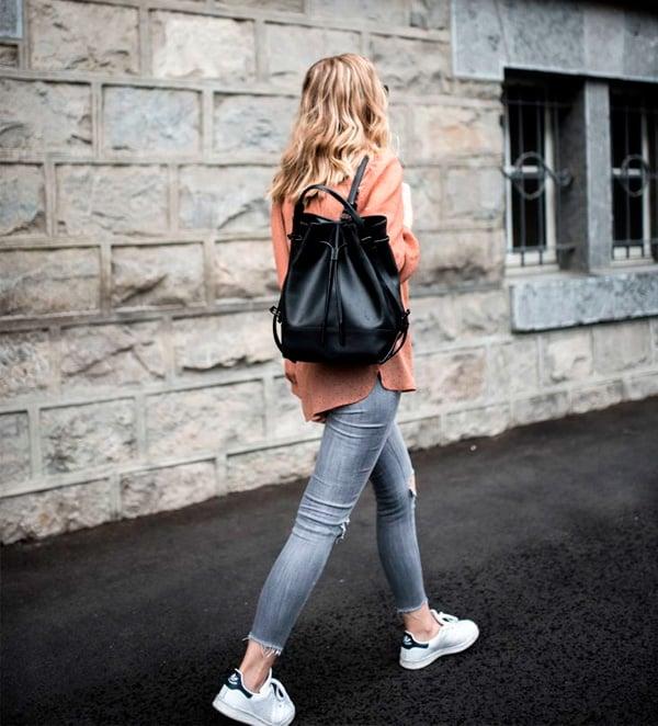 Chica caminando por la calle mientras usa un outfit casual y una mochila de color negro