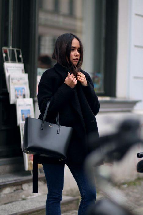 Chica caminando por la calle con un abrigo negro y bolso de color negro