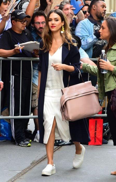 Jessica Alba caminando por la calle con un vestido blanco, blazer y bolso de color rosa