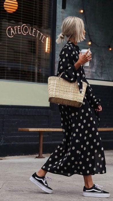 Chica usando un vestido largo con tenis y un bolso de paja