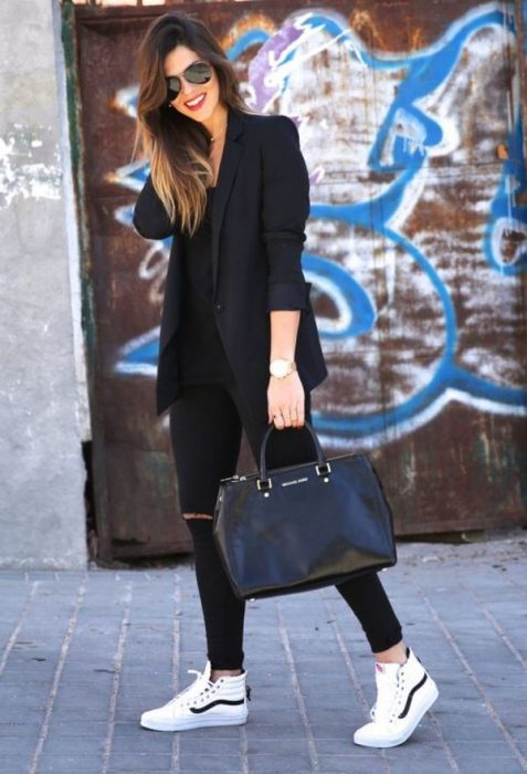 Chica usando un outfit negro con un bolso de mano en color negro