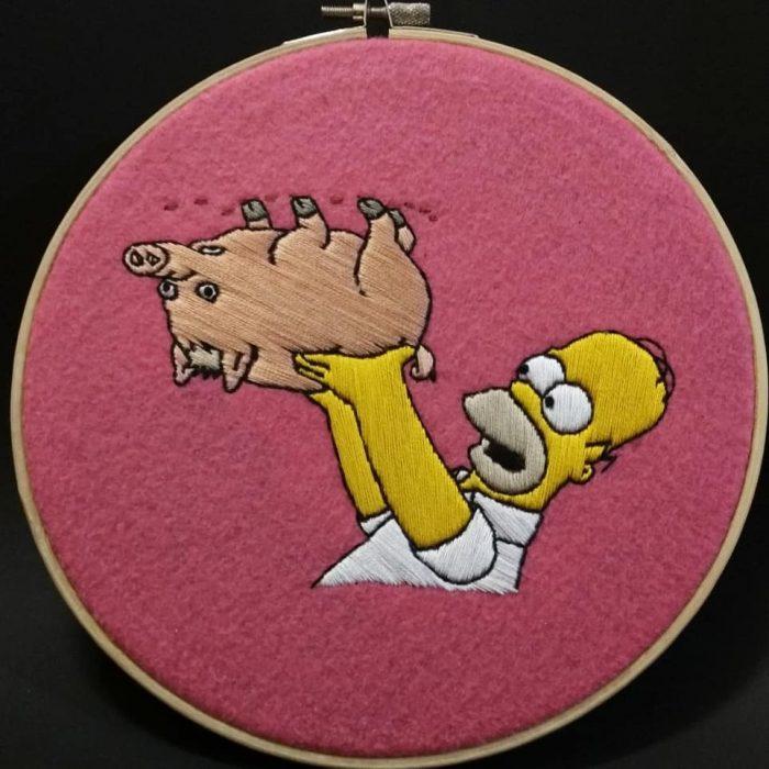 Bordado de Gabriela Martinez con escena de Los Simpson, Homero Simpson con el puerco araña