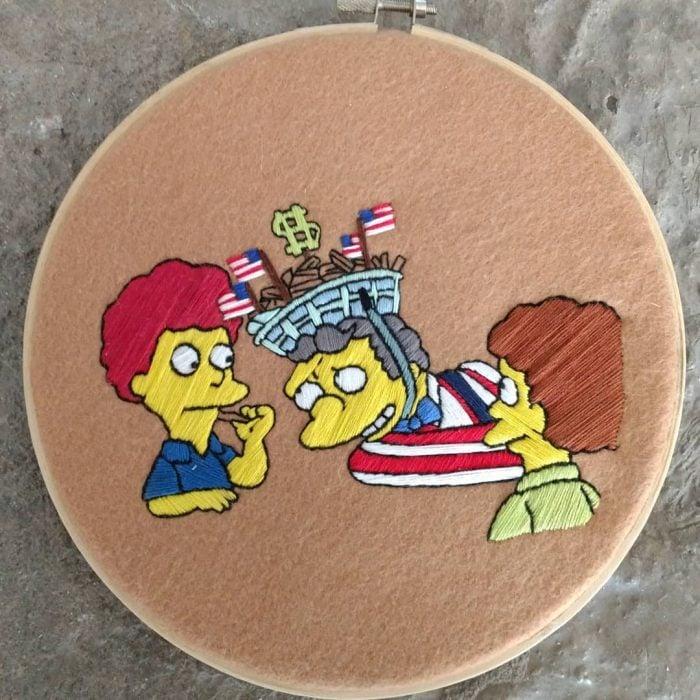 Bordado de Gabriela Martinez con escena de Los Simpson, Moe con una cesta de papas fritas en la cabeza