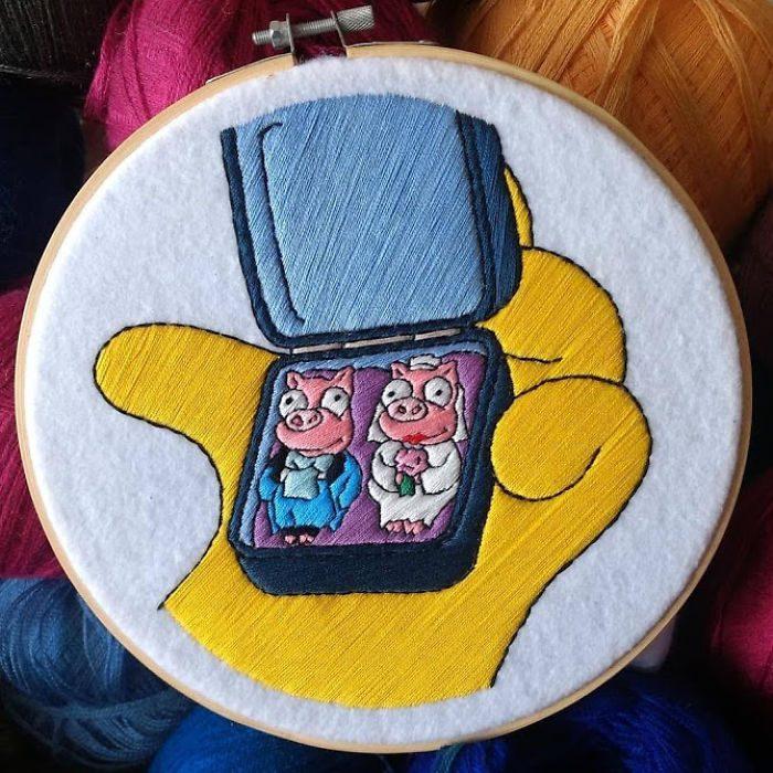 Bordado de Gabriela Martinez con escena de Los Simpson, Homero viendo los prendedores de cerditos
