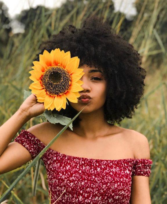 Mujer afroamericana con cabello chino esponjado en un campo con girasol en la mano