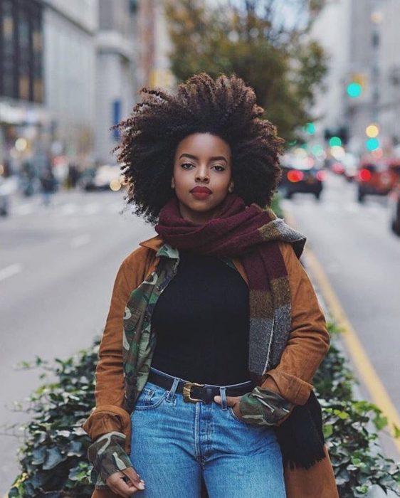 Chica afroamericana con cabello chino esponjado, posando para fotografía en la calle
