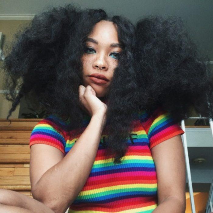 Chica afroamericana con rasgos asiáticos, ojos rasgados y pecas, con cabello chino, esponjado y con frizz