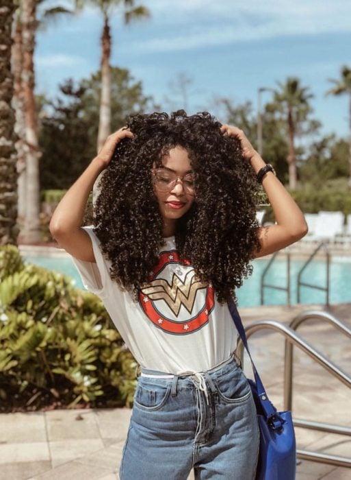 Chica afroamericana con cabello café, chino, esponjado y largo, con blusa de La mujer maravilla