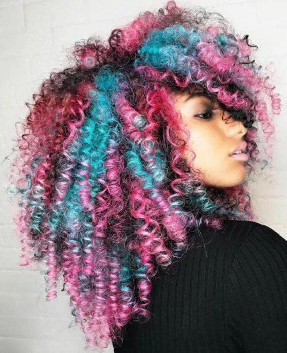 Chica afroamericana con cabello chino, esponjado y teñido de colores rosa y azul