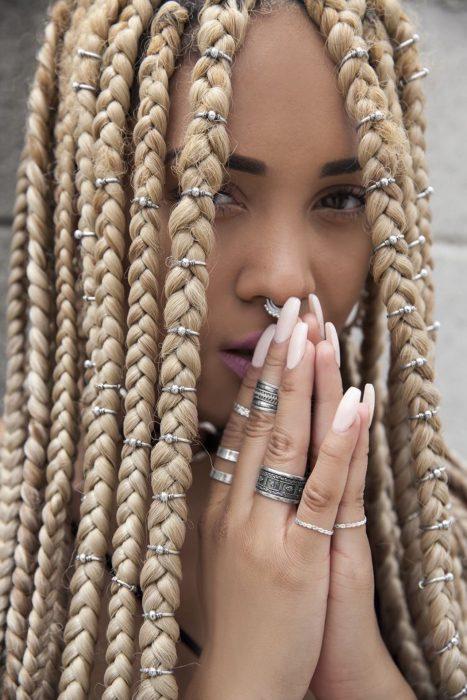 Chica afroamericana con cabello rubio, trenzas y argollas, uñas postizas rosas y varios anillos en los dedos